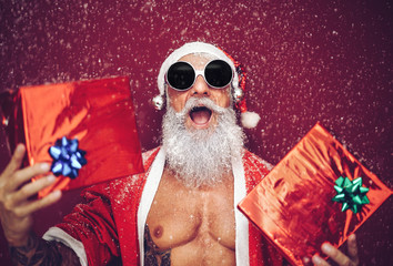 52130b4a0e05a Happy fit santa claus laughing and giving christmas gifts - Trendy beard  tattoo hipster senior wearing