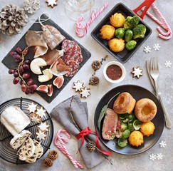 Christmas dinner table with roast beef,yorkshire pudding,appetizers platter and traditional cake. Christmass celebration, festive family dinner.  Overhead view.