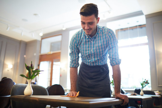 Young waiter in workwear wiping table with duster while preparing it for new guests