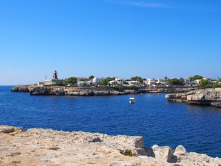 a view of Cala Santandria with lighthouse and boat in a bright summers day in Menorca Spain