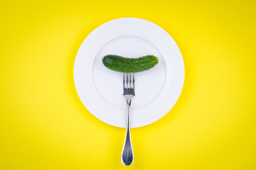 Fresh cucumber on fork. Colorful background