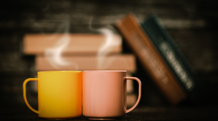 Two cups and books in bokeh on background.