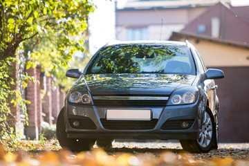 Front view of gray shiny empty car parked in quiet area on sunny autumn day wide at stone fence on blurred cottages and golden foliage bokeh background. Transportation and urban parking concept.