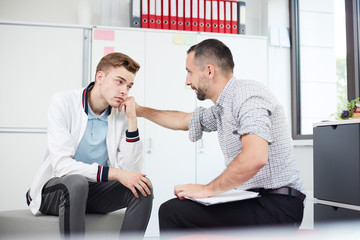 Professional psychologist comforting teenage guy while giving him piece of advice at session