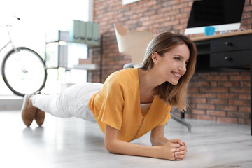 Beautiful young businesswoman doing exercises in office. Workplace fitness