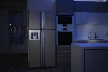Kitchen interior with four door refrigerator at night