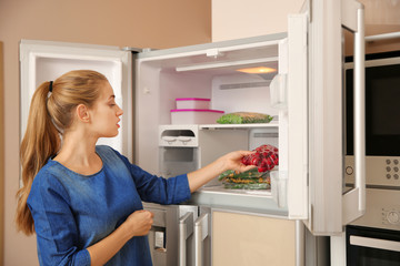 Young woman with frozen cherries near open refrigerator at home