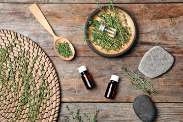 Flat lay composition with natural essential oil and thyme on wooden background