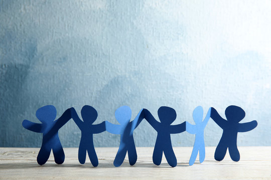 Paper people holding hands on wooden table. Unity and help concept