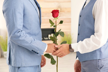 Happy newlywed gay couple with flower at home, closeup