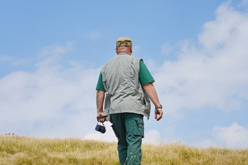 Traveler man photographed from the back in sports wear stands on the top of mountain. Blue sky with white clouds in a background.