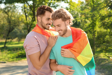 Happy gay couple with rainbow flag outdoors