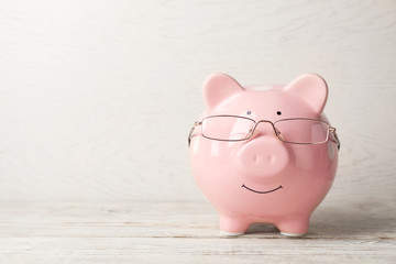 Piggy bank with glasses on light table. Space for text