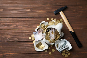 Broken piggy bank with money and hammer on wooden background, top view. Space for text