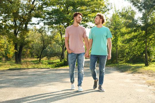 Happy gay couple walking in green park