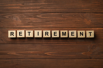 "Cubes with word ""RETIREMENT"" on wooden background. Pension planning concept"