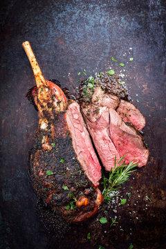 Traditionelle barbecue Lammkeule mit Knochen mit Gewürzen und Kräutern  als Draufsicht auf einem alten verrosteten Board