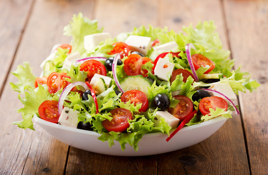 bowl of fresh salad with vegetables and greens