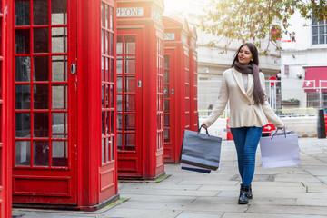 Shopping in London: attraktive Frau mit Einkaufstaschen läuft an roten Telefonzellen in London vorbei