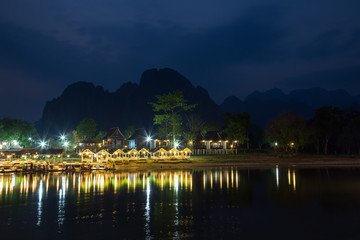 Several people at a lit waterfront restaurant by the the Nam Song River and silhouette of karst limestone mountains in Vang Vieng, Vientiane Province, Laos, at dusk.