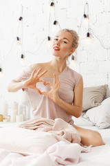 Young  fashionable blonde girl posing in home apartments. Woman makes gesture heart with fingers. Concept of Valentine's day and love. Modern bright home interior.