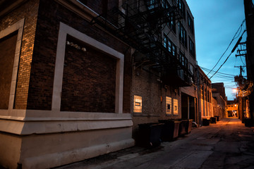 Fototapete - Dark and scary downtown urban city street corner alley with an e