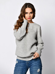 Young beautiful woman posing in new casual grey blouse sweater
