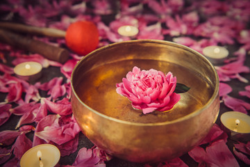 Tibetan singing bowl with floating inside in water pink peony flower. Burning candles, special sticks and petals on the black stone background. Meditation and Relax. Exotic massage. Selective focus.