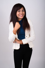 Studio shot of young happy Persian businesswoman smiling while l