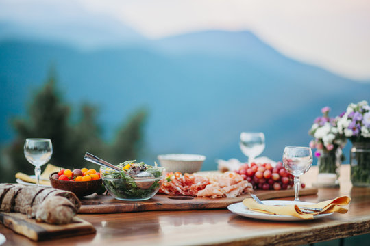 Salami platter and salad on a wooden table in the garden