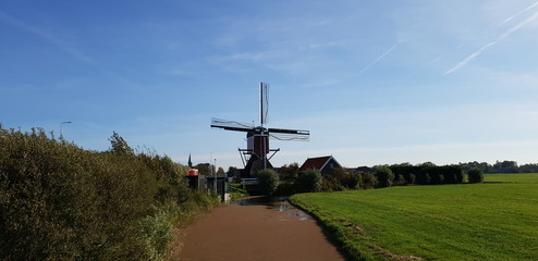 green meadows with ditch with water and old ancient windmill in the polder at Oude Ade in The Netherlands.