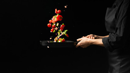 Chef preparing vegetables on a dark background on a grill pan