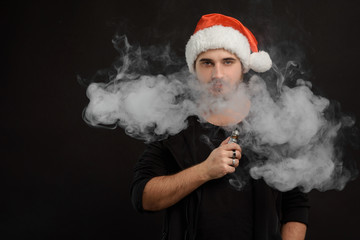 Man with beard in Santa red hat smoking electronic sigarette. vape pen. vape smoke. Christmas concept