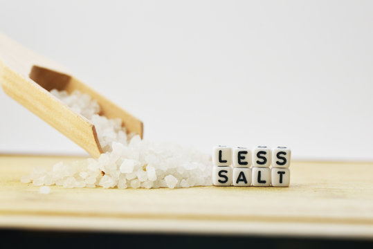 Eat less salt recommendation with plastic letters  and granulated salt on wooden chopping board