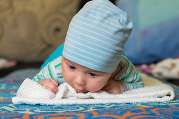 the baby with a cap is lying on the stomach and raising her head