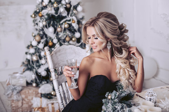 The blonde in a black dress with a glass sitting at the New Year's table looks to the side. Christmas tree in the background.