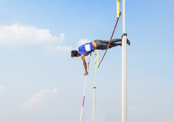 athlete pole vault pole jumping competition over bar in to the sky at stadium