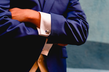 Crossed arms of businessman with blue suit.