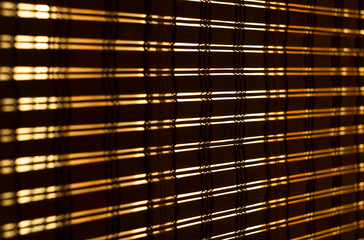 The interior of the home, sunlight shining through the bamboo blinds at the window.