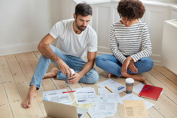 Image of multiethnic woman and man entrepreneurs work together on new business startup project, search information on website, collaborate together, sit on floor, creat employment application