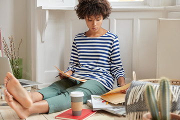 Photo of serious black young woman analyzes contract, drinks aromatic coffee, has attentive look, dressed in striped sweater, being bare foot, enjoys domestic calm atmopshere, uses technology