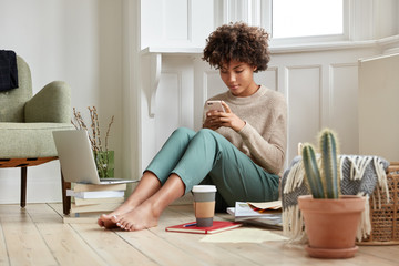 Photo of attractive busy woman has bushy hair, reads business data on cell phone, prepares for session, studies literature, surf internet on cell pone, makes notes in notepad, drinks coffee uses wifi