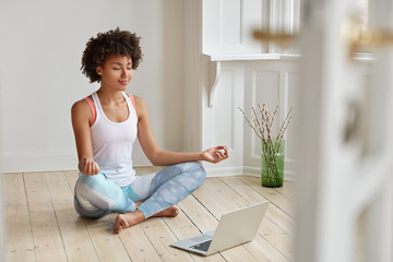 Calm lady with Afro hairstyle, dressed in sportswear, meditates on floor in empty room, listens spiritual practices lessons on laptop computer, poses in lotus pose, tries to relax. Yoga concept