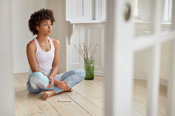 Photo of concentrated black woman sits crossed legs on wooden floor, has thoughtful expression, meditates indoor, modern cell phone near, listens calm pleasant music. People and wellbeing concept