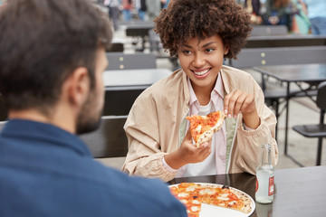 Photo of mixed race young family couple have tasty dish, eat delicious pizza in outdoor restaurant, drink energetic beverage, have friendly relationships. People, spare time and lunch concept.