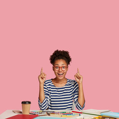 Astonished overjoyed black woman with Afro hair combed in bun, wears transparent glasses, points with both index finger upwards, shows free space for your advertising content against pink wall