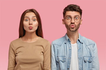 Portrait of attractive girlfriend and boyfriend make grimace, pout lips, have funny looks, dressed casually, stand shoulder to shoulder, model against pink background. Friendship, facial expressions
