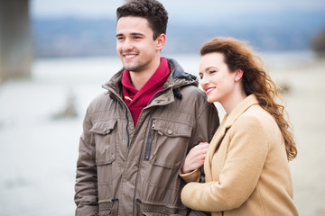Young beautiful couple together outdoors at windy weather