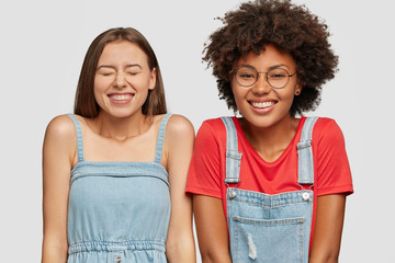 Studio shot of cheerful mixed race women laugh happily at good joke, have broad smiles, dressed in caual clothes, isolated over white background. Diverse classmates being in good mood, watch comedy