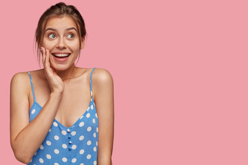 Picture of beautiful Caucasian woman looks joyfully upwards, keeps hand on cheek, being glad, dreams about something pleasant, dressed in blue polka dot dress, stands against pink studio wall